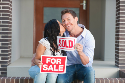 Happy couple holding for sale and sold signs kissing